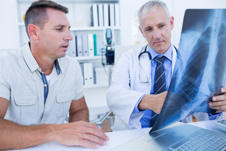 Doctor and patient looking at Xray in medical office