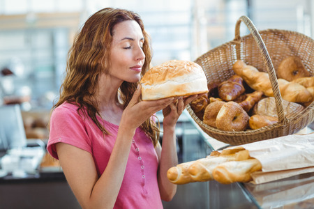 Pretty brunette smelling loaf of bread at the bakery