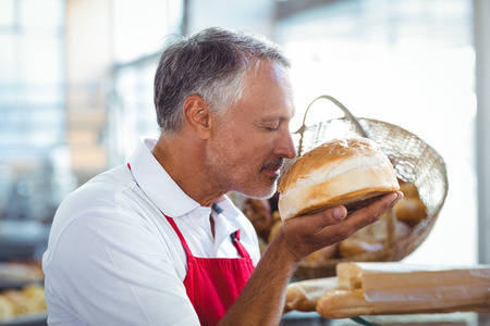 Waiter smelling freshly baked bread in the bakery