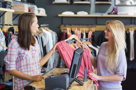 Foto de Smiling blonde doing shopping in clothes store - Imagen libre de derechos