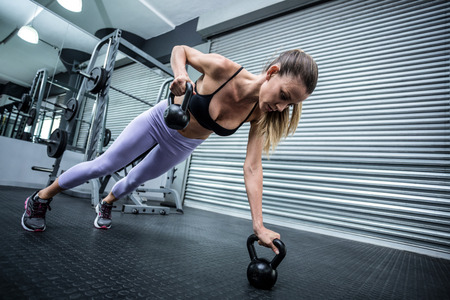 Muscular woman doing pushups while pulling kettlebells