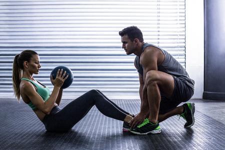 Foto für Side view of a muscular couple doing abdominal ball exercise - Lizenzfreies Bild