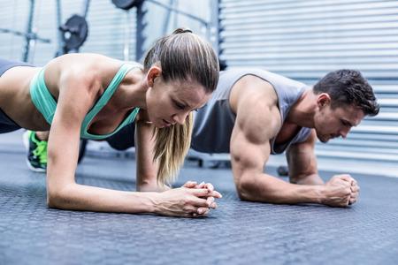 Foto de Side view of a muscular couple doing planking exercises - Imagen libre de derechos