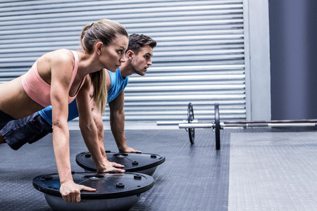 Photo for Side view of a muscular couple doing bosu ball exercises - Royalty Free Image