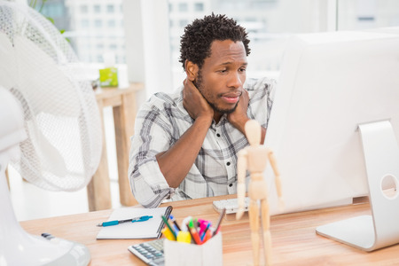 Young businessman looking at his computer screen in the office