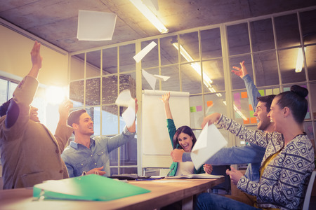 Photo pour Group of business people celebrating by throwing their business papers in the air - image libre de droit