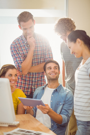 Creative business team gathered around a tablet in the officeの写真素材
