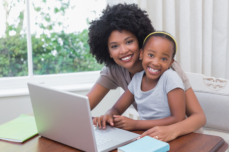 Happy mother and daughter using the laptop at home