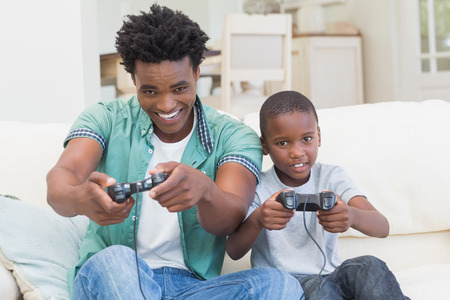 Father and son playing video games together at home in the living room