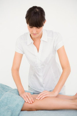 Female masseur massaging womans leg at spa center