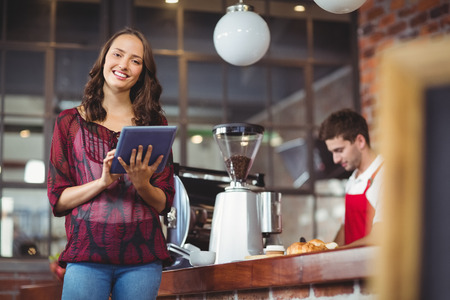 Foto de Portrait of a pretty woman using a tablet at the coffee shop - Imagen libre de derechos
