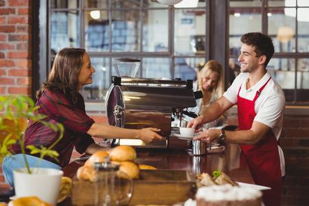 Photo pour A smiling barista serving a client at the coffee shop - image libre de droit