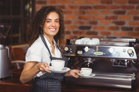 Portrait of smiling barista holding two cups of coffee at coffee shop