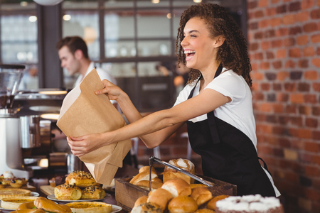Smiling waitress giving paper bag to customer at coffee shop