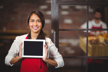Portrait of a waitress showing a digital tablet at the coffee shop