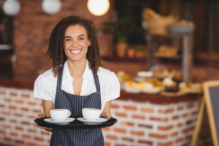 Photo pour Portrait of barista holding a tray of coffee cups at the coffee shop - image libre de droit