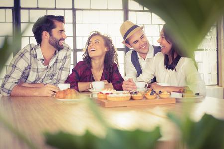 Foto de Laughing friends enjoying coffee and treats at coffee shop - Imagen libre de derechos
