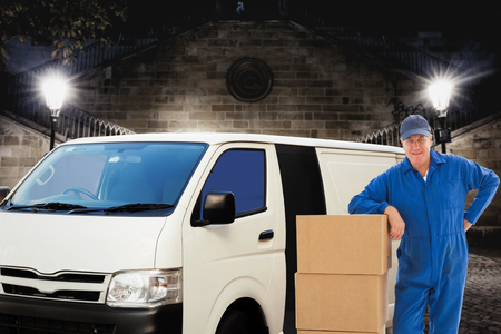 Happy delivery man leaning on pile of cardboard boxes against building by night