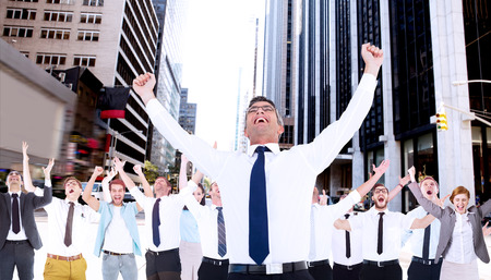 Excited businessman with glasses cheering against new york street