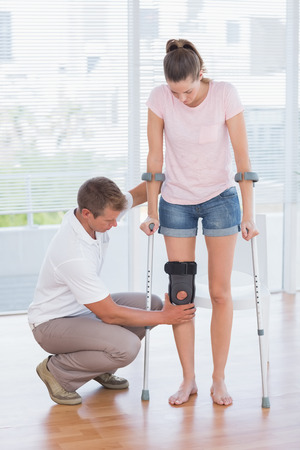 Doctor examining his patient knee in medical office