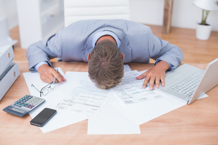 Photo pour Businessman being depressed by accounting in his office - image libre de droit