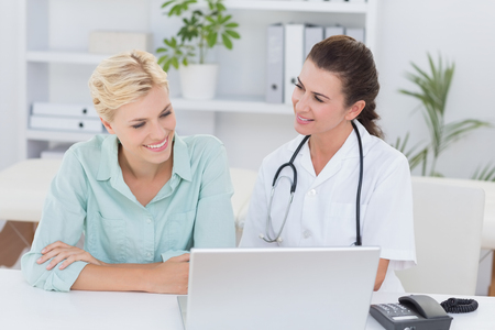 Patient and doctor looking at computer in medical office