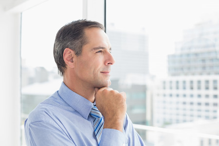 Thoughtful businessman looking away in his office