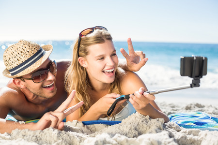 Happy couple taking selfie with selfie stick at the beach