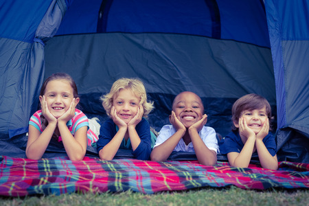 Smiling children lie down in the tent together in the park on a sunny day
