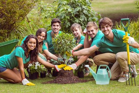 Photo pour Happy friends gardening for the community on a sunny day - image libre de droit
