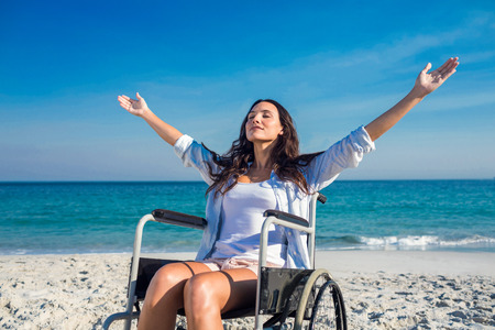 Disabled woman with arms outstretched at the beach on a sunny day