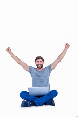 Happy handsome man cheering behind his computer on white background