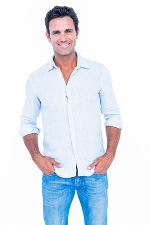 Happy handsome man looking at camera with hands in pocket on white background