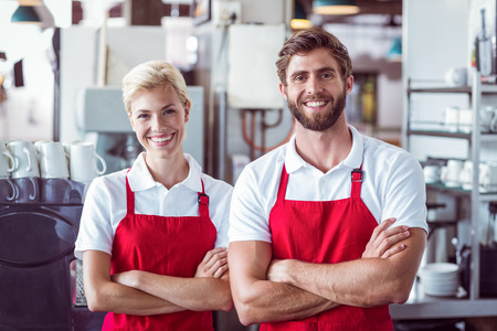 Photo for Two baristas smiling at the camera at the cafe - Royalty Free Image