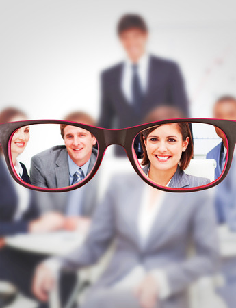 Glasses against happy business group having a meeting