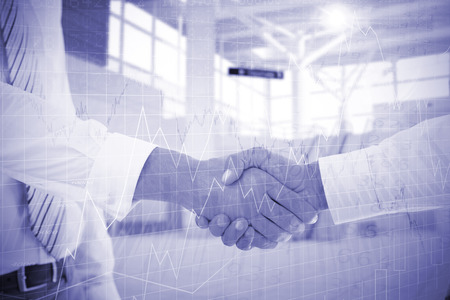 Close-up shot of a handshake in office against stocks and shares