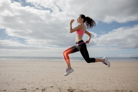 Digital composite of Highlighted leg bones of jogging woman on beach