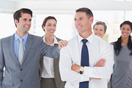 Business people congratulating their colleague in the office