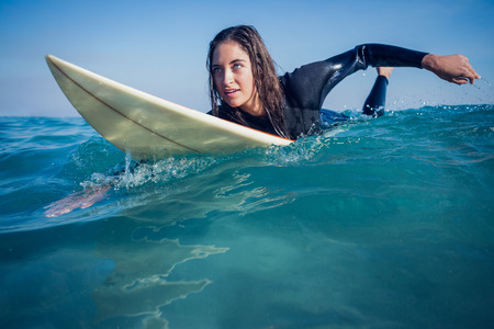 Photo pour woman in wetsuit with a surfboard on a sunny day at the beach - image libre de droit
