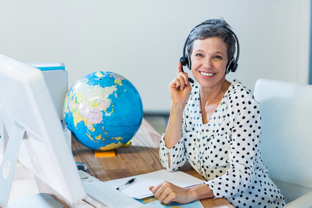 Smiling travel agent sitting at her desk in the office