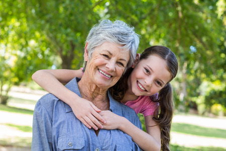 Photo pour granddaughter and grandmother smiling in a park on a sunny day - image libre de droit