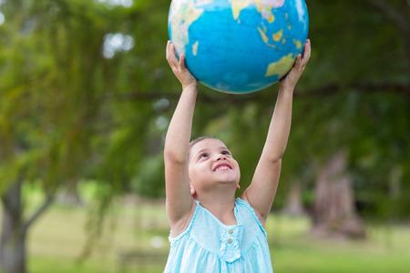 Photo pour Little girl holding a globe on a sunny day - image libre de droit