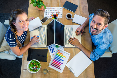 Smiling partners working at desk using laptop in the office