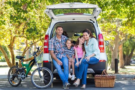 Foto de Happy family getting ready for road trip on a sunny day - Imagen libre de derechos