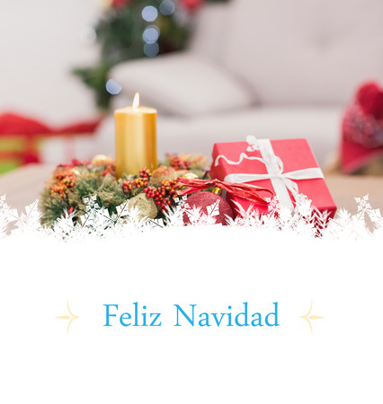 Candle and wreath on table for christmas against Christmas greeting card