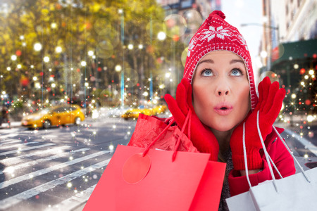Blonde in winter clothes holding shopping bags against blurry new york street