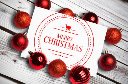 Banner and logo saying merry christmas against digitally generated grey wooden planks