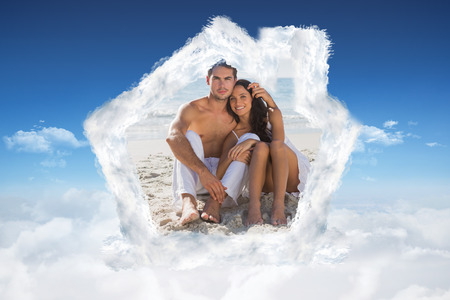 Cuddling couple smiling at camera against bright blue sky over clouds