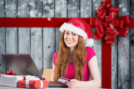 Festive redhead shopping online with laptop against wood with festive bow