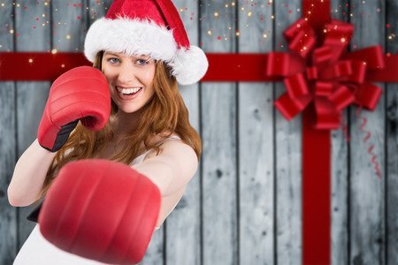 Festive redhead punching with boxing gloves against wood with festive bow